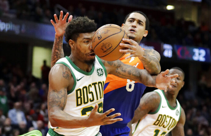 Boston Celtics' Marcus Smart, left, and Cleveland Cavaliers' Jordan Clarkson battle for a loose ball in the second half of an NBA basketball game, Tuesday, March 26, 2019, in Cleveland. Boston won 116-106. (AP Photo/Tony Dejak)