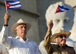 FILE - In this May 1, 2019 file photo, Cuba's President Miguel Diaz-Canel, left, and former Cuban President Raul Castro wave Cuban flags as they watch the annual May Day parade file past at Revolution Square in Havana, Cuba. On Monday, April 19, 2021, Cuba's Communist Party congress chose Díaz-Canel to be its leader, adding that post to the title of president he assumed in 2018, replacing his mentor Raul Castro and sealing a political dynasty that had held power since the 1959 revolution. (AP Photo/Ramon Espinosa, File)