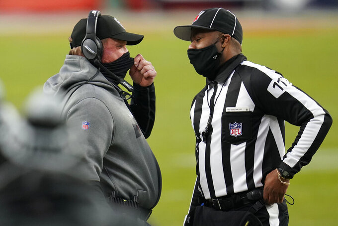 Las Vegas Raiders head coach Jon Gruden speaks with an official during the first half of an NFL football game against the Denver Broncos, Sunday, Jan. 3, 2021, in Denver. (AP Photo/David Zalubowski)