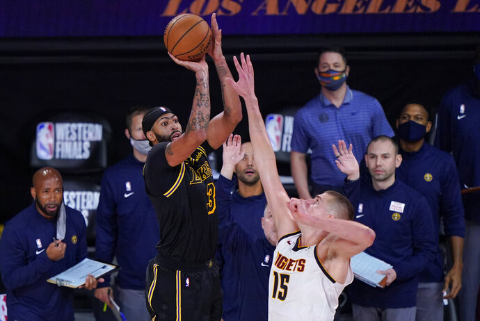 Los Angeles Lakers' Anthony Davis (3) shoots a 3-point basket over Denver Nuggets' Nikola Jokic (15) at the end of an NBA conference final playoff basketball game Sunday, Sept. 20, 2020, in Lake Buena Vista, Fla. The Lakers won 105-103. (AP Photo/Mark J. Terrill)