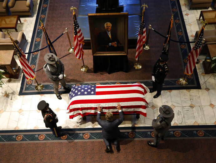 A member of the public prays over the casket of former U.S. Sen. Ernest