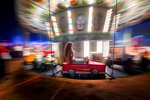 In this picture taken Saturday, Sept. 7, 2019, with a slow shutter speed, a little girl holds her hair while ridding in a merry go round at an autumn fair in Rosiorii de Vede, southern RomaniaRomania's autumn fairs are a loud and colorful reminder that summer has come to an end and, for many families in poorer areas of the country, one of the few affordable public entertainment events of the year. (AP Photo/Andreea Alexandru)