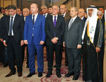 In this Monday, Dec. 2, 2019 photo, released by the Syrian official news agency SANA, the United Arab Emirates Charge d'affaires Abdul-Hakim Naimi, right, and Syria's Deputy Foreign Minister Faisal Mekdad, center, attend a ceremony to mark UAE's National Day, in Damascus, Syria. During the ceremony Naimi praised Syrian President Bashar Assad's