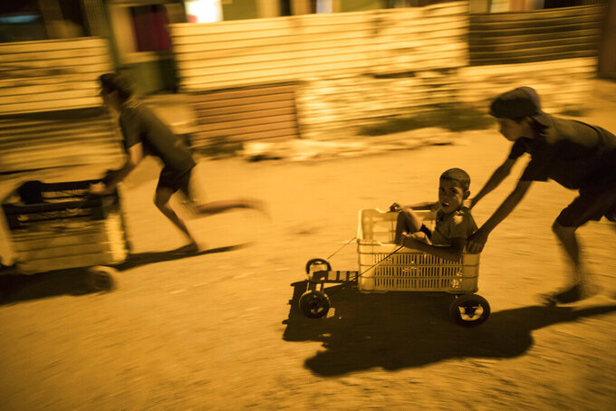 "In this Tuesday, Nov.19, 2019 photo, children race in makeshift go-carts in the ""Altos de Milagros Norte"" neighborhood of Maracaibo, Venezuela. Nationwide, an estimated 4.5 million residents have fled Venezuela, most going to nearby Colombia, Peru and Ecuador. They search for better jobs to send money home, but they often confront backlash and hardships as their numbers steadily grow. (AP Photo/Rodrigo Abd)"
