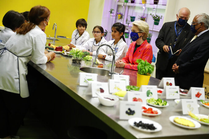 European Commission President Ursula von der Leyen, center, and Portuguese Prime Minister Antonio Costa, right, join schoolchildren in a kitchen lab at the Center for Living Science in Lisbon, Wednesday, June 16, 2021. The president of the European Commission has started in Lisbon a tour of some European Union capitals to announce the initial endorsement of their plans for spending the bloc's massive economic recovery fund. (AP Photo/Armando Franca)