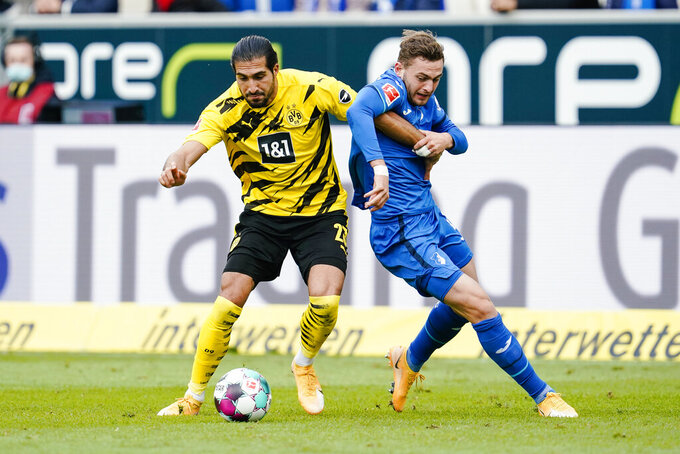 Dortmund's Emre Can, left, and Hoffenheim's Jacob Bruun Larsen compete for the ball during the German soccer Bundesliga match between TSG Hoffenheim and Borussia Dortmund in Sinsheim, Germany, Saturday, Oct. 17, 2020. (Uwe Anspach/dpa via AP)