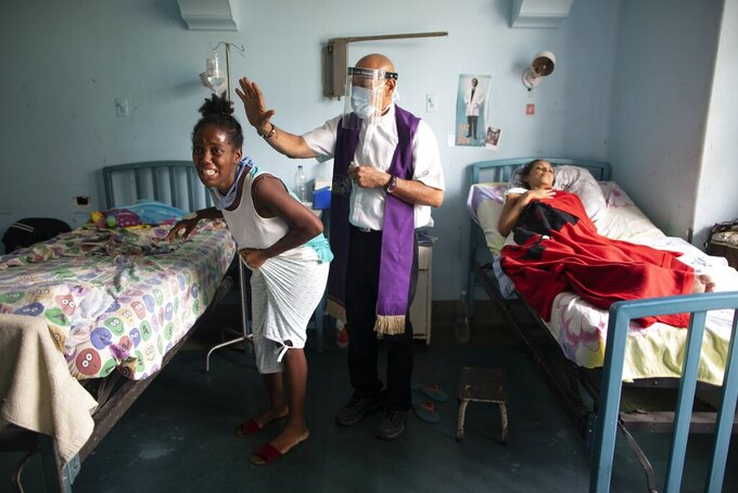 Father Felix Mendoza, a Venezuelan Catholic priest, center, prays over a woman who cries, saying she is in physical pain, at a public hospital in Caracas, Venezuela, Tuesday, May 11, 2021, amid the coronavirus pandemic. Father Felix has been visiting patients at the hospital to comfort the sick, for the last 20 years. (AP Photo/Ariana Cubillos)