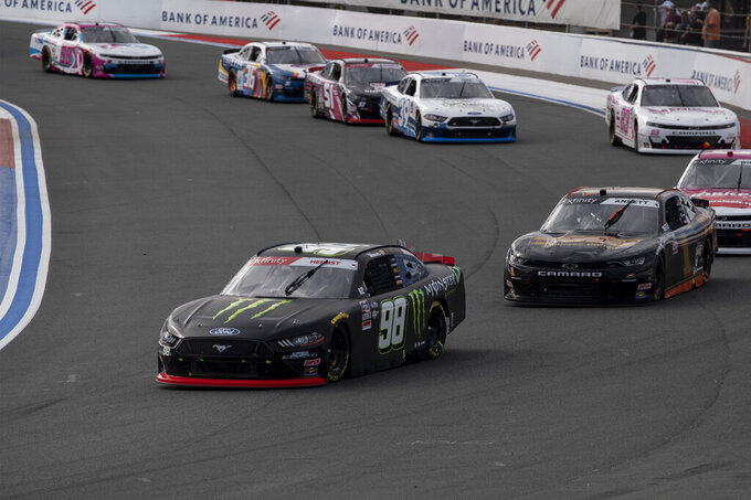 NASCAR Xfinity Series driver Riley Herbst (98) leads a pack of cars during the NASCAR Xfinity auto racing race at the Charlotte Motor Speedway Saturday, Oct. 9, 2021, in Concord, N.C. (AP Photo/Matt Kelley)
