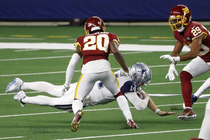Washington Football Team's Jimmy Moreland (20) and Kendall Fuller (29) move in as Dallas Cowboys quarterback Andy Dalton (14) dives forward after a short run for a first down in the second half of an NFL football game in Arlington, Texas, Thursday, Nov. 26, 2020. (AP Photo/Roger Steinman)