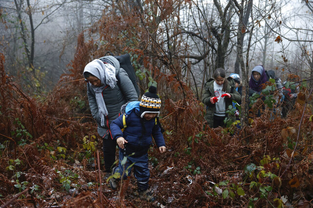 Alia and her 5-year old son walk through a Croatian forest with others after crossing the Bosnia-Croatia border near the Bosnian town of Velika Kladusa, Thursday Dec. 10, 2020. Entire migrant families are on the move in cold weather in Bosnia while trying to reach the West as the European Union warns the Balkan country it must act to prevent a humanitarian disaster. A statement by the EU Bosnia mission says current weather conditions are putting at risk the lives of more than 3,000 people sleeping rough or staying in inadequate conditions. (AP Photo/Marc Sanye)