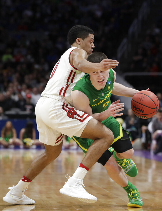 Oregon guard Payton Pritchard (3) drives against Wisconsin guard D'Mitrik Trice during the first half of a first-round game in the NCAA men's college basketball tournament March 22, 2019, in San Jose, Calif. (AP Photo/Chris Carlson)