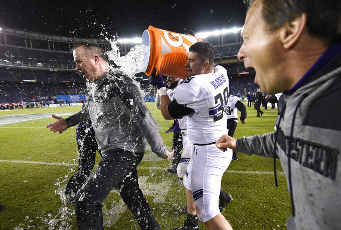 Northwestern offensive lineman Trey Klock (39) douses head coach Pat Fitzgerald as time runs out during the Holiday Bowl NCAA college football game against Utah, Monday, Dec. 31, 2018, in San Diego. (AP Photo/Denis Poroy)