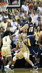 UNC-Greensboro guard Francis Alonso (10) drives to the basket over Wofford forwards Chevez Goodwin (1) and Cameron Jackson (33) in the first half of an NCAA college basketball game for the Southern Conference tournament championship, Monday, March 11, 2019, in Asheville, N.C. (AP Photo/Kathy Kmonicek)