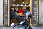Customers have a drink at a restaurant in Beirut, Lebanon, Monday, May 4, 2020. Lebanon is entering a new phase of the lockdown Monday, allowing, barber shops, car showrooms and restaurants to open at 30% capacity during the day. (AP Photo/Hassan Ammar)