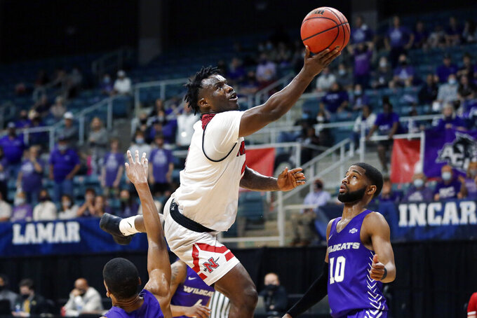 Nicholls State guard Ty Gordon shoots between Abilene Christian forward Joe Pleasant, left, and guard Reggie Miller (10) during the second half of an NCAA college basketball game for the Southland Conference men's tournament championship Saturday, March 13, 2021, in Katy, Texas. (AP Photo/Michael Wyke)