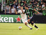 Austin FC midfielder Cecilio Dominguez, right, drives the ball upfield against Los Angeles midfielder Daniel Crisostomo, left, during the first half of an MLS soccer match, Wednesday, Sept. 15, 2021, in Austin, Texas. (AP Photo/Michael Thomas)