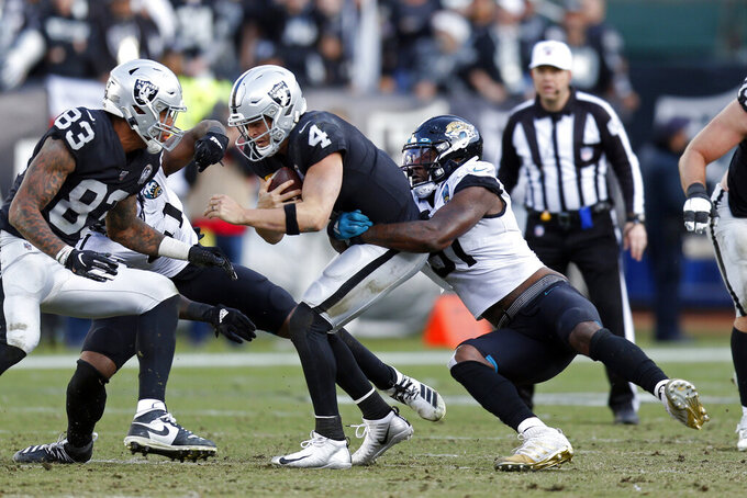 Oakland Raiders quarterback Derek Carr (4) is sacked by Jacksonville Jaguars defensive end Yannick Ngakoue as Raiders tight end Darren Waller (83) looks on during the second half of an NFL football game in Oakland, Calif., Sunday, Dec. 15, 2019. (AP Photo/D. Ross Cameron)