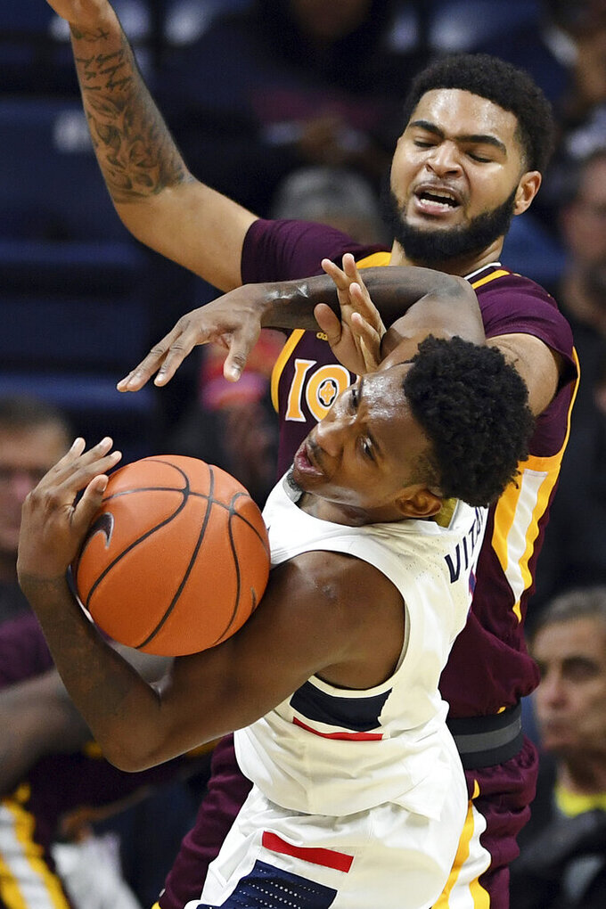 Connecticut's Christian Vital and Iona's E.J. Crawford fight for possession of the ball in the first half of an NCAA college basketball game, Wednesday, Dec. 4, 2019, in Storrs, Conn. (AP Photo/Jessica Hill)