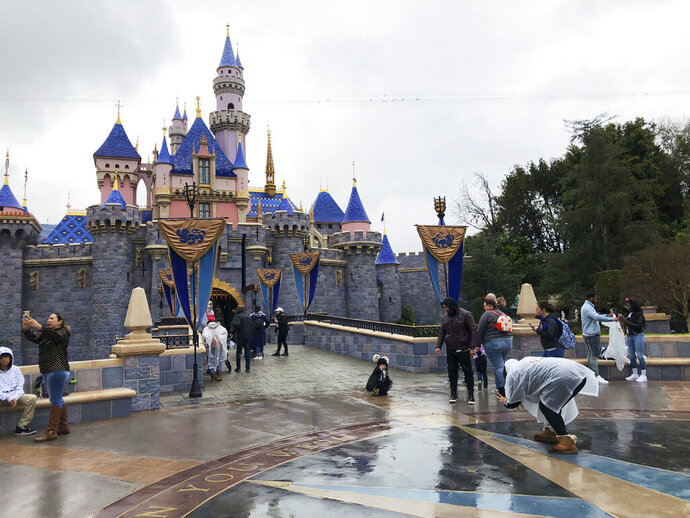 """FILE - In this March 13, 2020 file photo, visitors take photos at Disneyland in Anaheim, Calif.  Jungle Cruise, one of the original Disney parks' rides, is getting a 21st century remodel in yet the latest update to a legacy theme park ride that has been criticized in years past for being racially insensitive. The ride will updated by Disney """"imagineers"""