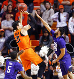Oklahoma State's Lindy Waters III (21) shoots between TCU's Alex Robinson (25), right, and Kendric Davis (5) in the second half of a NCAA college basketball game in Stillwater, Okla., Monday, Feb. 18, 2019. (Nate Billings/The Oklahoman via AP)