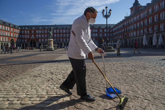 A waiter wearing a face mask to prevent the spread of coronavirus sweeps the terrace of a bar in downtown Madrid, Spain, Friday, Oct. 9, 2020. Spanish Prime Minister Pedro Sanchez is holding a Cabinet meeting to consider declaring a state of emergency for Madrid in order to impose stronger anti-virus restrictions on reluctant regional authorities. (AP Photo/Manu Fernandez)