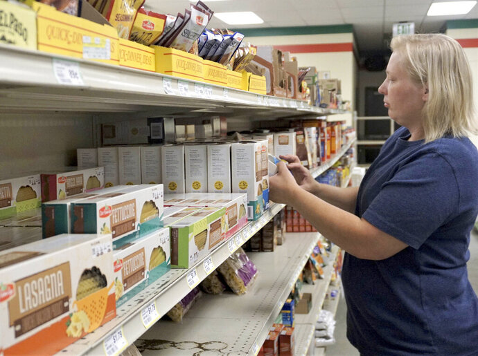 In this July 29, 2019 photo Colleen Bibelheimer, an employee at D&M Grocery in Drake, N.D. organizes a grocery shelf. North Dakota lawmakers want to study how the state can serve groceries in rural areas where shops have been closing. State Sen. Jim Dotzenrod, D-Wyndmere, sponsored the legislative study resolution that calls for an investigation into the distribution and transportation of food in the state. The Minot Daily News reports that the town of Drake is likely to lose its only grocery beginning next year. Closure will mean customers will have to drive 30 miles to Harvey or Velva for the nearest grocery. (Jill Schramm/Minot Daily News via AP)