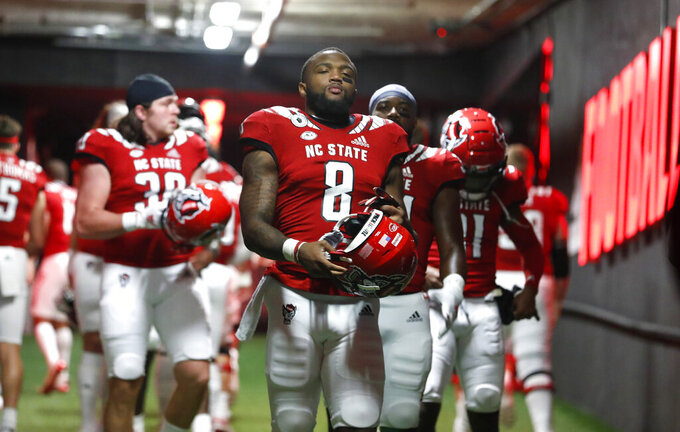 FILE - In this Nov. 21, 2020 file photo, North Carolina State running back Ricky Person Jr. (8) and teammates head to the field to warm up before an NCAA college football game against Liberty in Raleigh, N.C.  North Carolina State (8-3) is a 2 ½-point underdog against Kentucky (4-6) in the TaxSlayer Gator Bowl, a number the Wolfpack consider a slight heading into Saturday, Jan. 2, 2021 game in Jacksonville.   (Ethan Hyman/The News & Observer via AP, Pool)