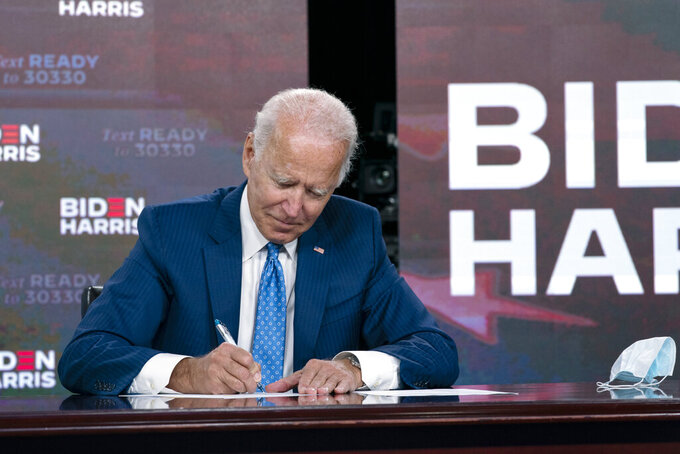 Democratic presidential candidate former Vice President Joe Biden signs a required documents for receiving the Democratic nomination for President of the United States in Wilmington, Del., Friday, Aug. 14, 2020. (AP Photo/Carolyn Kaster)