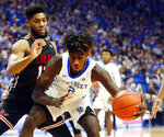 Kentucky's Kahlil Whitney (2) looks for an opening in the defense of Lamar's V.J. Holmes, left, during the first half of an NCAA college basketball game in Lexington, Ky., Sunday, Nov. 24, 2019. (AP Photo/James Crisp)