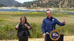 FILE - In this July 8, 2021, file photo, California Gov. Gavin Newsom and sign interpreter Julia Townsend stand at the edge of a diminished Lopez Lake near Arroyo Grande, Calif. California regulators on Tuesday, Aug. 3 said some farmers in one of the country's most important agricultural regions will have to stop taking water out of major rivers and streams because of a severe drought that is rapidly depleting the state's reservoirs and killing endangered species of fish. (David Middlecamp/The Tribune (of San Luis Obispo) via AP, File)