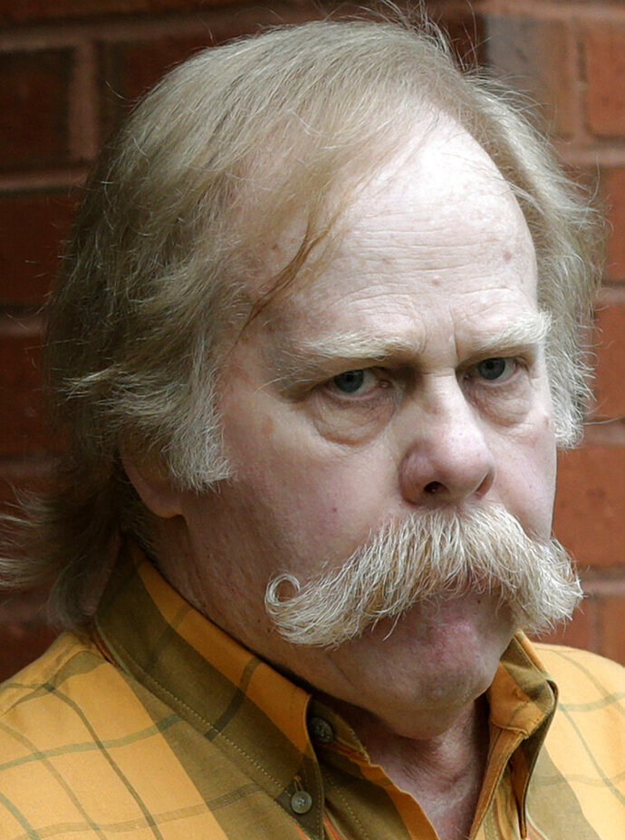 FILE - In this June 10, 2013 file photo, University of Alabama fan Harvey Updyke departs the Lee County Justice Center in Opelika, Ala., after pleading guilty earlier to poisoning landmark oak trees at Auburn University. Updyke has died. He was 71. (AP Photo/Dave Martin, File).