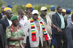 Zimbabwean President Emmerson Mnangagwa, center, visits Chimanimani, about 600km south east of Harare, Zimbabwe, Wednesday March 20, 2019. Mnangagwa visited a part of Chimanimnani affected by cyclone Idai and promised assitance in the form of food and rebuilding of homes. Hundreds are dead, many more missing and thousands at risk from massive flooding in Mozambique, Malawi and Zimbabwe caused by Cyclone Idai. (AP Photo/Tsvangirayi Mukwazhi)