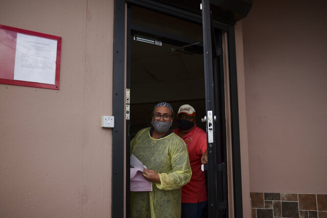 Sandra Algarin and Efrain Ortiz, employees at a health clinic, peek out the door while wearing masks as a precaution against COVID-19, in Canovanas, Puerto Rico, Thursday, May 21, 2020. Puerto Rico is cautiously reopening beaches, restaurants, churches, malls, and hair salons under strict conditions as the U.S. territory emerges from a two-month lockdown despite dozens of new coronavirus cases reported daily. (AP Photo/Carlos Giusti) PUERTO RICO OUT-NO PUBLICAR EN PUERTO RICO
