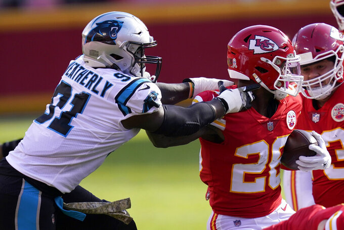 Carolina Panthers defensive end Stephen Weatherly, left, reaches for Kansas City Chiefs running back Le'Veon Bell during the first half of an NFL football game in Kansas City, Mo., Sunday, Nov. 8, 2020. (AP Photo/Orlin Wagner)