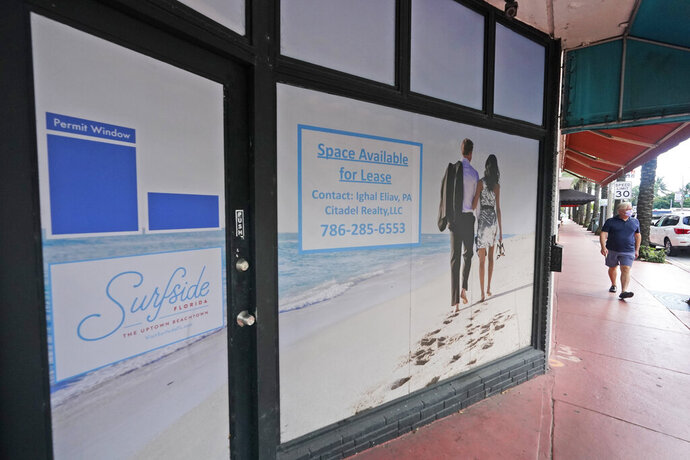 A pedestrian walks past an empty business available for lease, Monday, Oct. 12, 2020, in downtown Surfside, Fla.  The pandemic and recession are squeezing big apartment building owners, with a surge in vacancies leading to a decline in rent growth for the first time in years. The U.S. vacancy rate for apartments rose to 5% in the third quarter, the highest level in eight years, according to Moody's Analytics REIS.  (AP Photo/Wilfredo Lee)