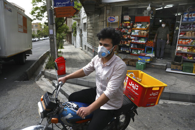 In this Tuesday, April 21, 2020 photo, grocery delivery man Saeed Vatanparast, wearing a protective face mask to help prevent the spread of the coronavirus, leaves on his motorcycle for a delivery, in Tehran, Iran. For some $15 a day, deliverymen don masks and gloves in Iran's capital to zip across its pandemic-subdued streets to drop off groceries and food for those sheltering at home from the virus. (AP Photo/Vahid Salemi)