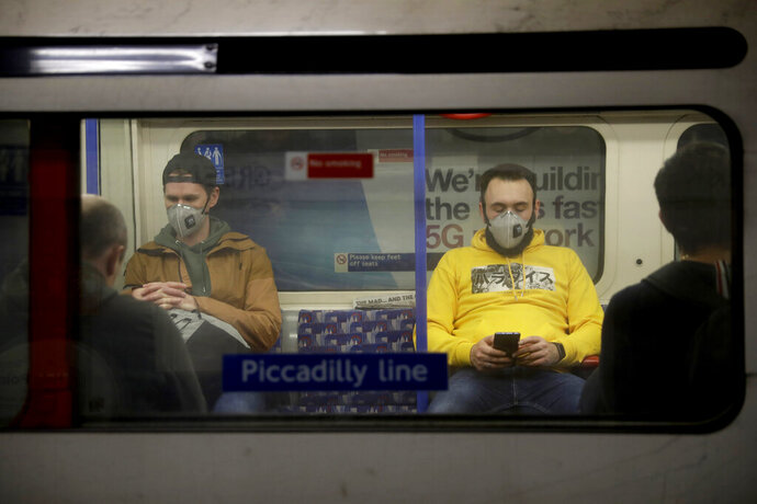 FILE - In this Friday, March 20, 2020 file photo, passengers wearing face masks travel on a Piccadilly Line underground train in London. The World Health Organization on Friday June 5, 2020, broadened its recommendations for the use of masks during the coronavirus pandemic and is now advising that in areas where the virus is spreading, people should wear fabric masks when social distancing is not possible, such as on public transport and in shops. (AP Photo/Matt Dunham, File)