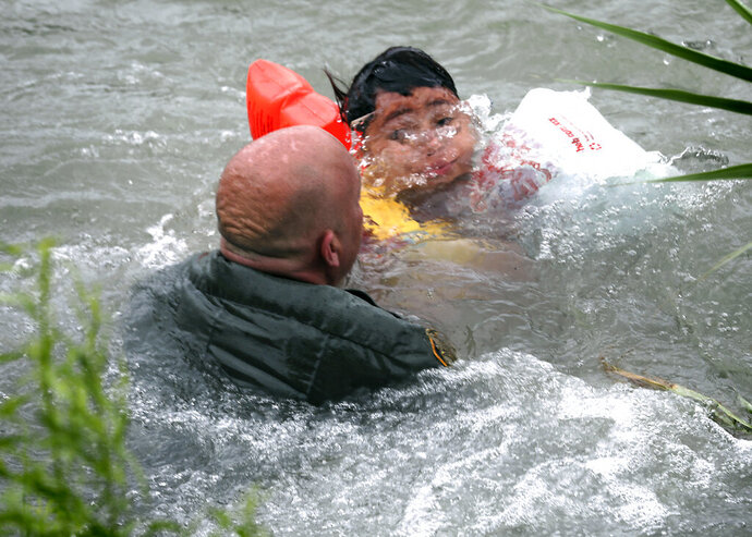 In this Friday, May 10, 2019 photo, Border Patrol Agent Brady Waikel rescues a 7-year-old boy from Honduras after he fell out of a makeshift raft and lost hold of his mother as Border Patrol agents respond to rafts crossing the Rio Grande River near Eagle Pass, Texas. (Bob Owen/The San Antonio Express-News via AP)