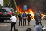 FILE - In this Tuesday, Jan. 15, 2019 file photo, security forces help civilians flee the scene as cars burn behind, at a luxury hotel complex attacked by the al-Shabab extremist group in Nairobi, Kenya. U.N. experts said in a report circulated Tuesday, Nov. 12, 2019 that al-Shabab extremists in Somalia remain