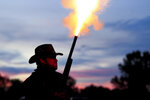 Cast member Dean Stout fires a blank bullet out of his shotgun as he attempts to scare visitors waiting in line to enter Terror Town, Saturday, Oct. 17, 2020, in Williamsburg, Ohio. Dean portrays a sheriff of the town protecting from the cult that has moved into the area. (AP Photo/Aaron Doster)