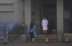 Hospital staff stand outside the emergency entrance of Wuhan Medical Treatment Center, where some infected with a new virus are being treated, in Wuhan, China, Wednesday, Jan. 22, 2020. The number of cases of a new coronavirus from Wuhan has risen to over 400 in China health authorities said Wednesday. (AP Photo/Dake Kang)
