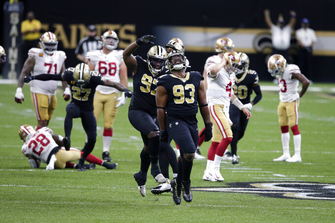 New Orleans Saints defensive tackle David Onyemata (93), defensive tackle Malcolm Roach (97) and strong safety Malcolm Jenkins (27) celebrate a defensive stop on fourth down in the first half of an NFL football game against the San Francisco 49ers in New Orleans, Sunday, Nov. 15, 2020. (AP Photo/Butch Dill)