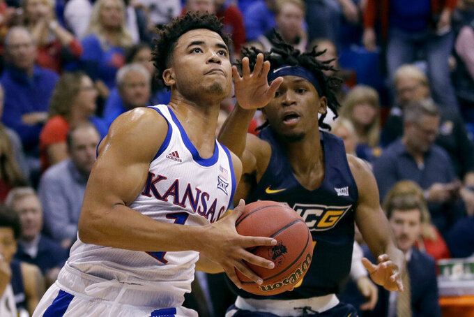 Kansas' Devon Dotson (1) gets past UNC Greensboro's Keyshaun Langley during the first half of an NCAA college basketball game Friday, Nov. 8, 2019, in Lawrence, Kan. (AP Photo/Charlie Riedel)