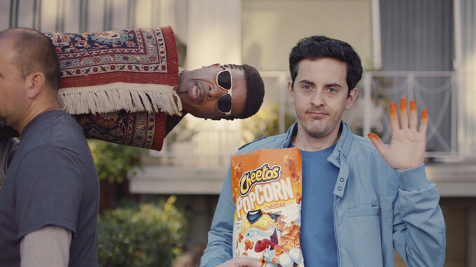 """This undated image provided by Cheetos shows MC Hammer in a scene from the company's 2020 Super Bowl NFL football spot. """"U Can't Touch This"""" is 30 years old this year but just as familiar as ever. (Cheetos via AP)"""