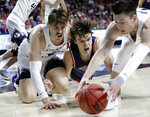 Saint Mary's Alex Ducas, center, and BYU's Zac Seljaas, left, and Alex Barcello reach for a loose ball during the first half of an NCAA college basketball game in the West Coast Conference tournament, Monday, March 9, 2020, in Las Vegas. (AP Photo/Isaac Brekken)