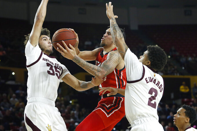 Utah forward Timmy Allen, center, drives to the basket between Arizona State's Taeshon Cherry (35) and Rob Edwards (2) during the first half of an NCAA college basketball game Saturday, Jan. 18, 2020, in Tempe, Ariz. (AP Photo/Ralph Freso)