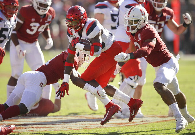 Arizona's Nathan Tilford, center, rushes against Stanford in the second half of an NCAA college football game Saturday, Oct. 26, 2019, in Stanford, Calif. (AP Photo/Ben Margot)