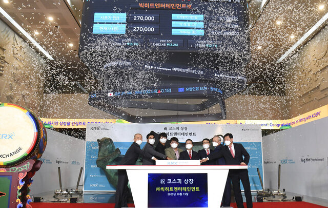 Big Hit Entertainment Ltd.'s Chairman and CEO Bang Si-Hyuk, fourth from left, poses with other participants for the media during the listing ceremony of the company at the Korea Exchange in Seoul, South Korea, Thursday, Oct. 15, 2020. The company, that manages boy band BTS made its market debut amid criticism by Chinese internet users after the group's leader thanked Korean War veterans for their sacrifices. (Korea Pool/Yonhap via AP)