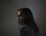 """Suzy Ishkontana, 7, poses for a portrait in the house of a family member where she is currently living after her house was destroyed in an airstrike during an 11-day war in Gaza City, Wednesday, June 16, 2021. Suzy's mother, her two brothers and two sisters -- ages 9 to 2 -- died in the May 16 Israeli attack on the densely packed al-Wahda Street in Gaza City. Israeli authorities say the bombs' target was Hamas tunnels; 42 people died, including 16 women and 10 children. """"My kids who died and my wife, they are now in a safe place and there is no worry about them, but my greater fear is for Suzy,"""" says her father, Riad Ishkontana. (AP Photo/Felipe Dana)"""