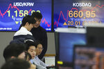 Currency traders watch monitors at the foreign exchange dealing room of the KEB Hana Bank headquarters in Seoul, South Korea, Thursday, Jan. 9, 2020. Asian stock markets rebounded Thursday as anxiety over potential U.S.-Iranian conflict eased. (AP Photo/Ahn Young-joon)